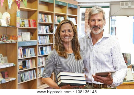 Male And Female Owners Of Bookstore Using Digital Tablet