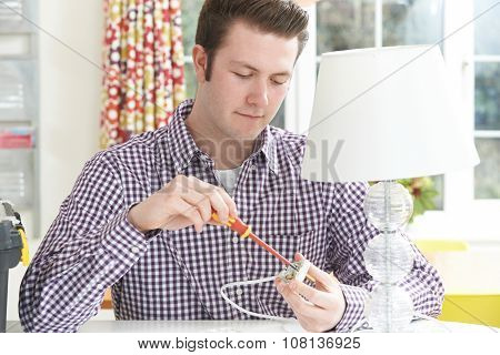 Man Wiring Electrical Plug On Lamp At Home