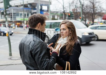 Couple In Jackets Communicating On Street Side