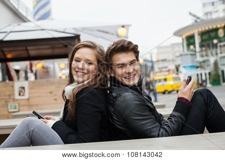 Couple Holding Mobile Phones While Sitting Back To Back