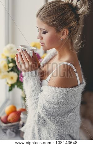 Pensive woman with Cup of hot tea standing at the window
