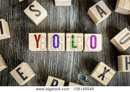 Wooden Blocks with the text: YOLO (You Only Live Once)