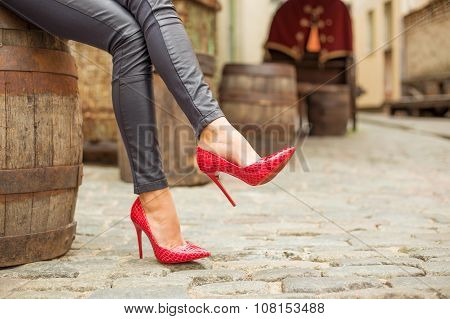 Lady in black leather pants and red high heel shoes