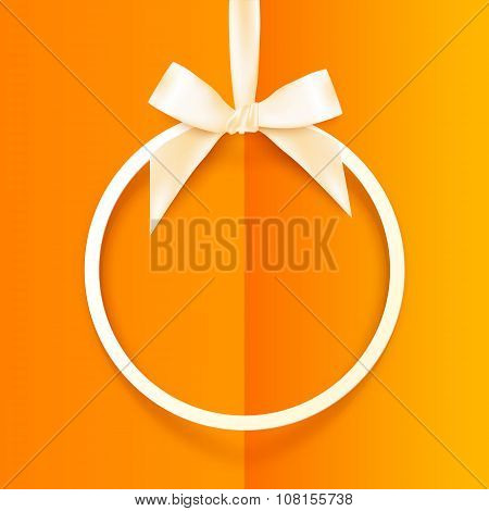 White round hanging frame with silky bow and ribbon  on orange background