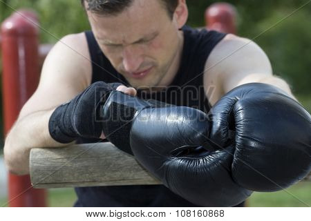 Kickboxer or muay thai fighter equips and trains outdoor.