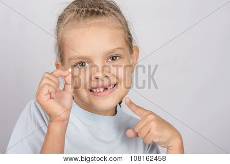 Six Year Old Girl With A Smile, Pointing At The Fallen Baby Tooth