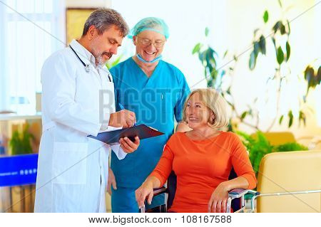 Happy Doctor And Surgeon Consulting Patient About Treatment Before Discharging From Hospital