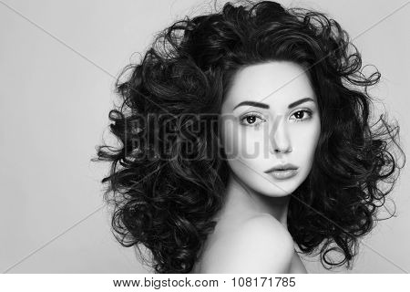 Black and white shot of young beautiful woman with long curly hair