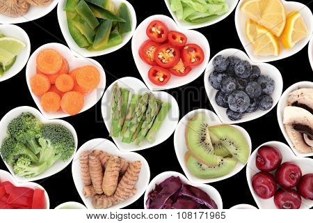 Superfood fruit and vegetable selection in heart shaped porcelain dishes over black background, high in vitamins and antioxidants.