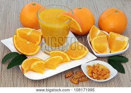 Freshly squeezed orange juice and vitamin c tablets with oranges over bamboo background.