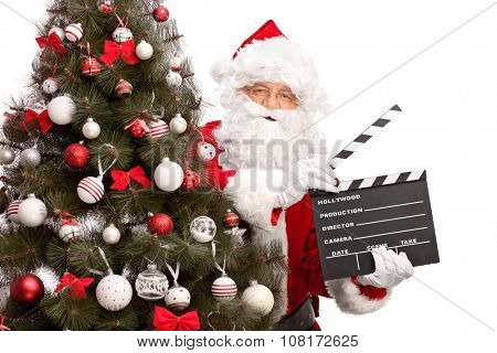 Santa Claus posing behind a Christmas tree and holding a movie clapperboard isolated on white background