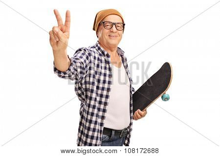 Studio shot of a senior skater holding a skateboard and making a peace sign with his hand isolated on white background