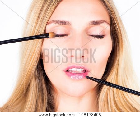 Make-up artist applying shadows and shine with cosmetic brushes