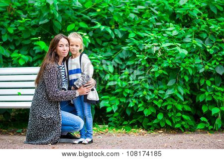 Happy mother and adorable little girl enjoying warm weather at beautiful park