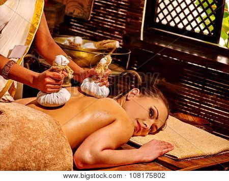 Woman having Ayurveda massage with herbal ball in India spa salon.