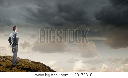 Rear view of confident businessman standing on rock top
