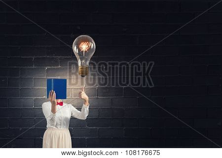 Woman with opened book against her face showing thumb up