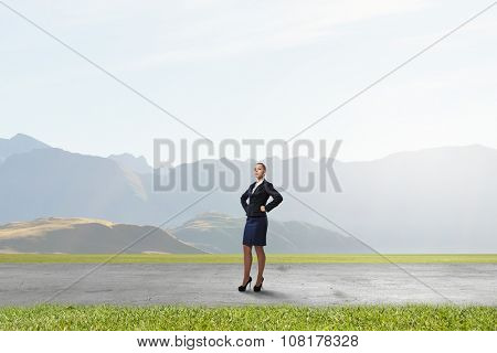 Young confident businesswoman with hands on waist