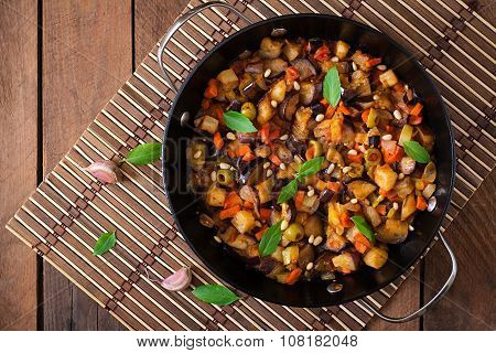 Italian Caponata with frying pan on a wooden background. Top view