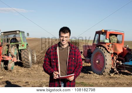 Farmer With Tractors On Field