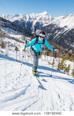 Young woman ascending a slope on skis.