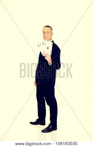 Full length elegant business man with four aces.