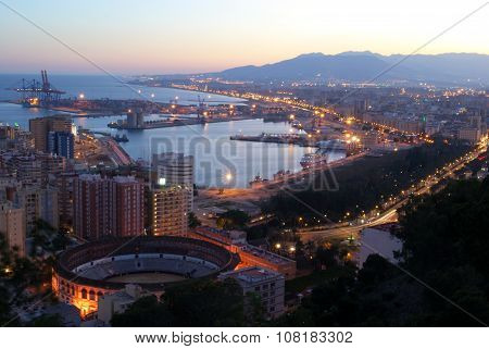 Malaga port and bullring at dusk.