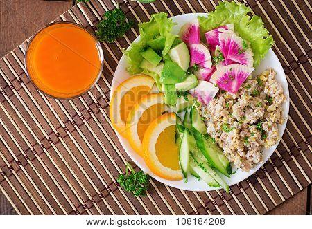 Dietary menu. Breakfast. Oatmeal porridge with vegetables (cucumber, avocado, daikon) and orange.