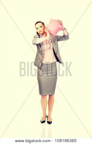 Caucasian businesswoman shaking a piggybank.
