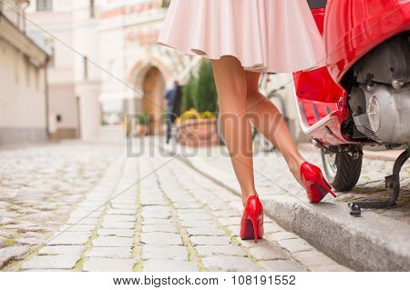 Woman in high heels standing next to stylish red moto scooter
