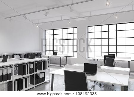 Workplaces In A Bright Modern Loft Open Space Office. Tables Equipped With Laptops; Corporate Docume