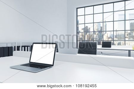 Workplaces In A Bright Modern Loft Open Space Office. Tables Equipped With Laptops, White Copy Space