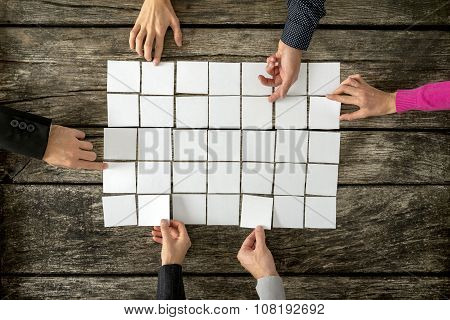 Top View Of Six Hands, Male And Female, Assembling A Collage Of Blank White Cards