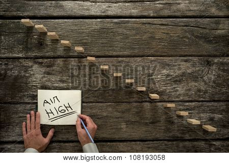 Male Hand Writing An Aim High Message On A White Paper Next To A Steps Made Of Wooden Pegs