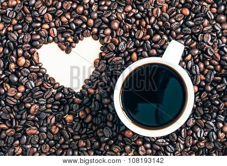 Espresso coffee cup and wooden spoon with heart shape coffee beans background.