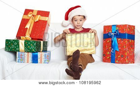 boy in red santa helper hat open gift boxes - christmas holiday concept