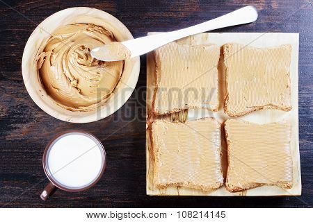Sandwiches With Peanut Butter On Wooden Plate, Peanut Butter In A Wooden Bowl, Table Knife, Milk In