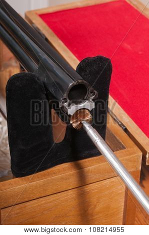 Cleaning an over/under style shotgun, inserting the brush on the cleaning rod into the lower chamber from the breach end