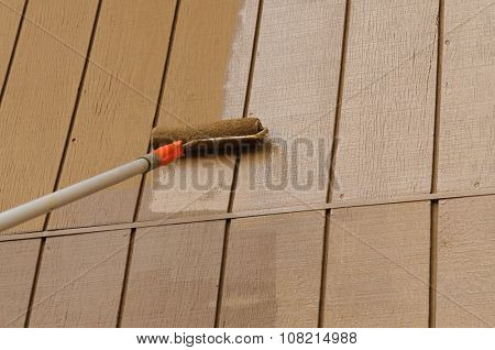 Using a roller applicator on an extension arm to paint the siding of a house