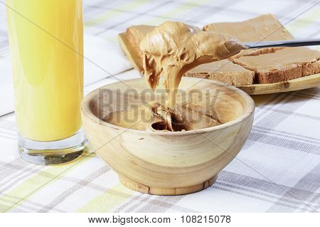 Sandwiches With Peanut Butter On Wooden Plate, Peanut Butter In A Wooden Bowl, Table Knife, Orange J