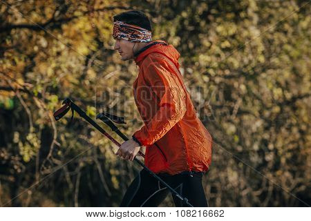 young man runner running marathon walking sticks