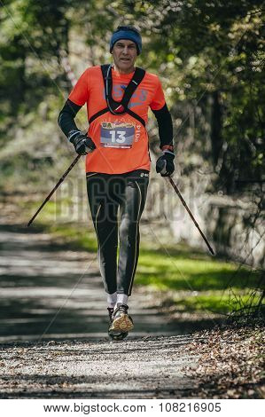 elderly athlete runs with sticks to walk distance of race