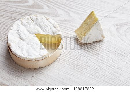 Camembert With Piece Of It , Isolated On White Brushed Farm Table