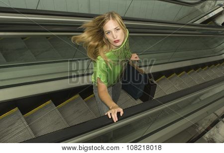 Portrait of blonde standing in the mall escalator after doing shopping.