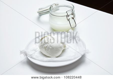 Fresh Buffalo Mozzarella In Front Of Jar With Brine Isolated Side View