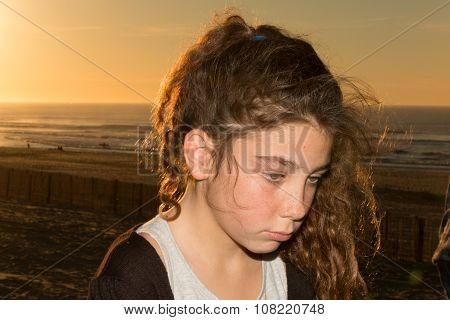 Beautiful Little Sad Girl Sitting On Sand  Beach.