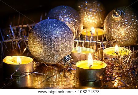 Burning Small Candles And Christmas Tree Decorations Against A Dark Background