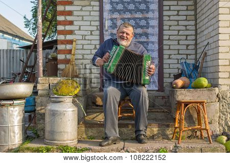 Ukrainian peasant playing button accordion (garmon) at the doorway