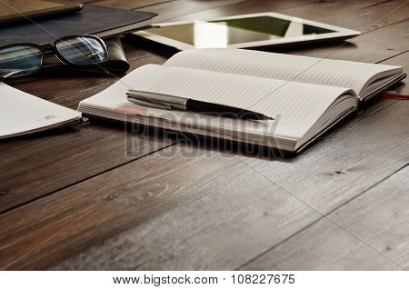 Open Notepad With A Pen On A Wooden Office Table