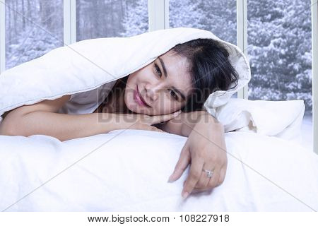 Female Model Lying On Bed Under Blanket